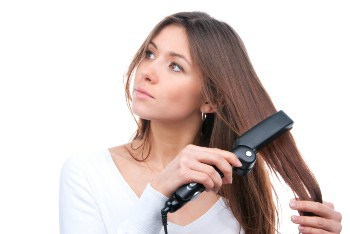 women styling her hair with straightener with built in comb